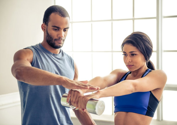 woman assisted by gym instructor