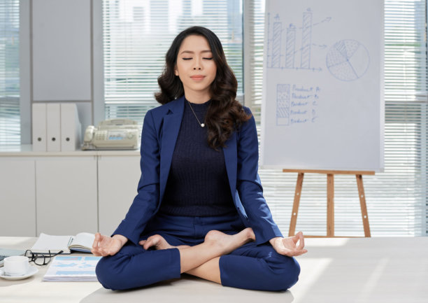 Full length portrait of attractive Asian businesswoman sitting on office desk in lotus position while doing yoga in order to relieve stress