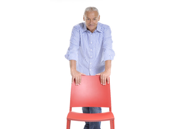 Senior man holding a red chair