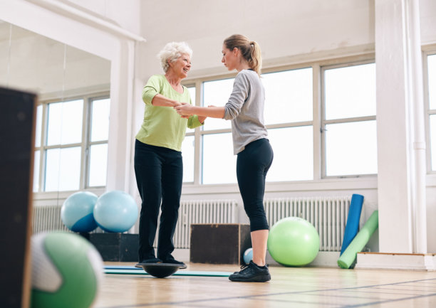 Elder woman being assisted by gym instructor while workout session.