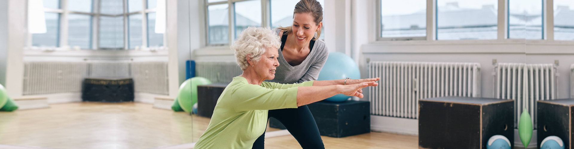 a senior woman exercising with her personal trainer